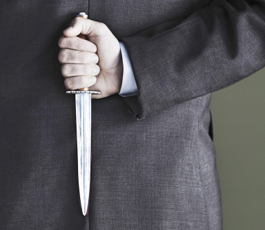 Closeup midsection of businessman holding knife against black ba